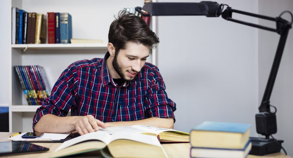 Student Reading Books at a Desk